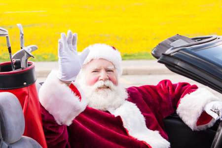 saint nick: Santa waves on his way to the golf course from his convertible with the top down Stock Photo
