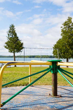 swing set: sunny summer day at Berford Lake park. An empty roundabout in forground with swing set overlooking the lake.