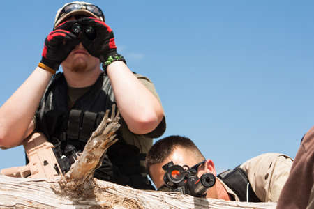 counter terrorism: One officer scoping out the area with binoculars while the second man focuses the target in his site