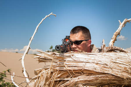 counter terrorism: Tactical special ops sniper behind cover of a tree stump in desert terrain Stock Photo