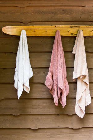 swimming towels hang from a vintage water ski rack at the cottage in summer 版權商用圖片