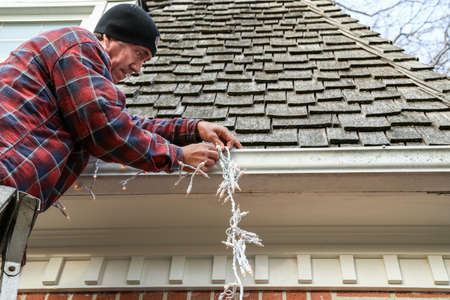 Zijaanzicht van een huiseigenaar op een ladder opknoping lichten op de buitenkant van zijn huis