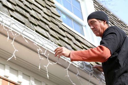a man hanging Christmas lights on the exterior of a house Stock Photo