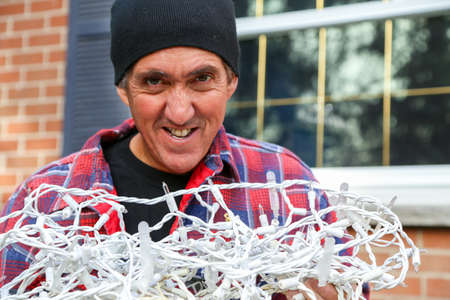 displeasure: about to tackle the dreaded job of untangling the Christmas lights and hanging them Stock Photo