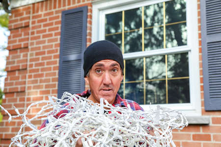 home owner: Home owner  looks dubious as he begins the annual chore of putting up the lights