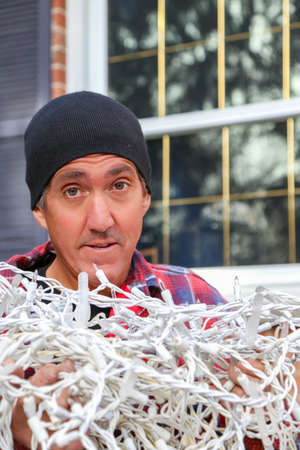 home owner: holding a huge tangled pile of Christmas lights this home owner prepares for the dreaded light hanging project