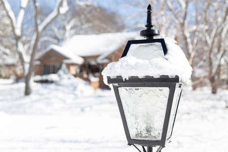 suburban neighborhood: coach style lightpost in focus against a suburban neighborhood under a blanket of winter snow Stock Photo