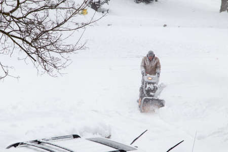 bundled: a man all bundled up in a heavy coat clearing snow in the driveway with a snow blower