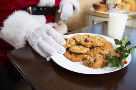 Santas hand reaching in to take a chocolate chip cookie from a plate