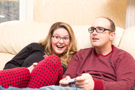 gamers: young woman laughs as she beats her partner at a video game