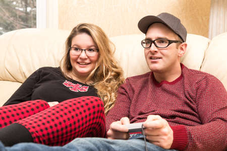 young adult couple sitting on the livingroom sofa using video controller while focused on the video game that is off screen Stock Photo