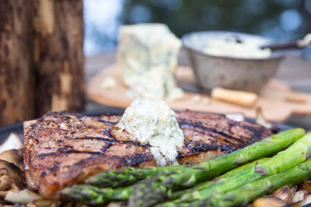 juicy steak dinner served outdoors with blue cheese butter melting over