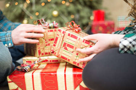 Christmas gift exchange stock photos royalty free christmas gift close up on a young couple sitting on the floor as they exchange christmas gifts negle Choice Image