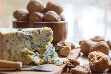 Delicious gourmet snack tray contains a chunk of blue veined Stilton cheese on a wood platter surrounded by walnuts in the shells and dried figs