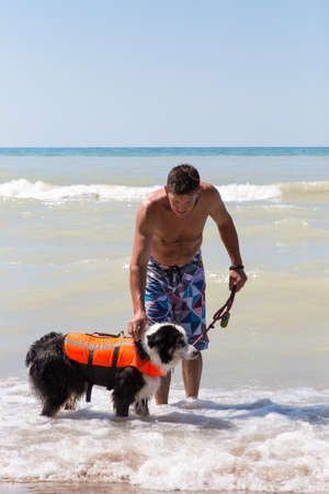 Man holding onto his older dog  in a life jacket as he prepares to swim at the Pinery provincial park on Lake Huron in Ontario Canada Standard-Bild
