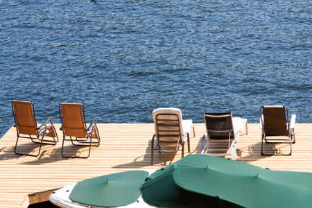 Boat in its slip at the newly finished dock. An assortment of lawn chairs sit facing out to Lake of Bays on a sunny afternoon at the cottage. 版權商用圖片
