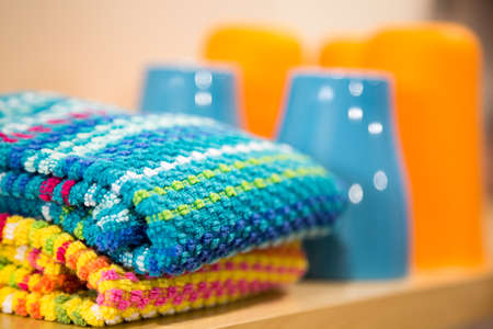 shallow focus on brightly colored kitchen towels folded on a shelf beside matching cups