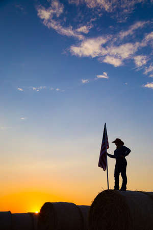 silhouette of a young woman in cowboy hat stands on a hay bale with an American flag overlooking farm land at sunset