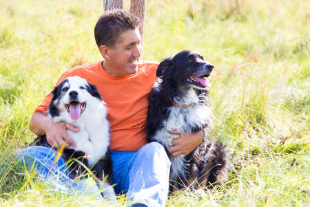 Sitting in the field on a warm fall day am an takes a break from a walk with his Australian Shepherd dogs, giving them a hug Stock Photo