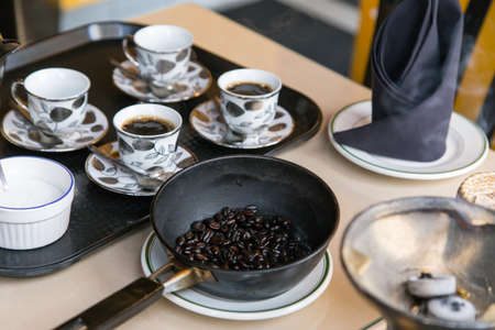 The traditional Ethiopian coffee service involves burning of incense, roasting fresh beans in a skillet and pouring from a tall carafe from a specified height.