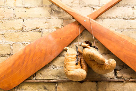 Vintage boxing gloves hang from paddles on a rustic yellow brick wall