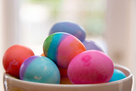 Close up bowl of brightly colored Easter eggs on diplay Standard-Bild