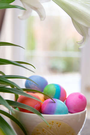 Bowl of brightly colored Easter eggs on diplay in kitchen window