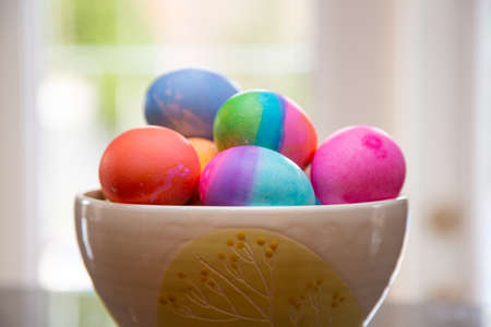 Bowl of brightly colored Easter eggs on diplay