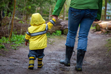 Mother and toddler going for a walk on a muddy trail wearing boots and raincoats Standard-Bild