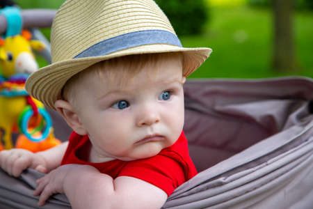 cute baby boy wearing a hat sitting looking out the side of his stoller