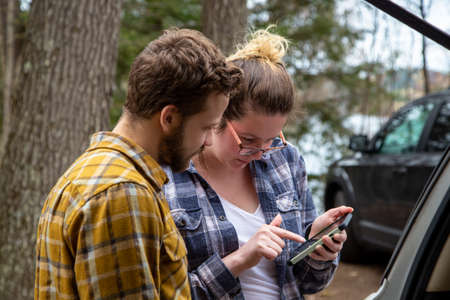 travelers consulting gps and guide on a smart phone outdoors at the cottage