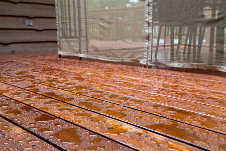 Water beads up on a freshly sealed wood deck after a morning rainstorm at the cottage. Standard-Bild