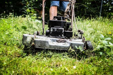Redneck cottage lawnmower pushes through thick grass and weeds. Standard-Bild