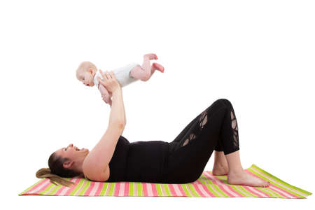mother with baby having fun holding baby in the air while laying on a fitness mat