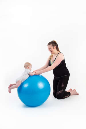 mother with baby suspended holding his head up on a gymnastic ball