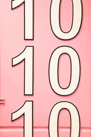 number ten multiple times on pink wall Stock Photo