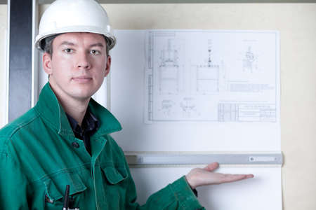 Professional engineer standing by the adjustable board and showing his drawing photo