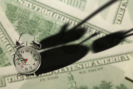Time is money  Alarm clock, throwing deep shadow on money background Stock Photo - 13165000