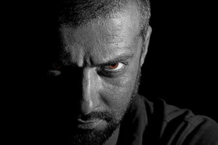 venganza: Veiw dram�tico de un hombre cara en la oscuridad Foto de archivo