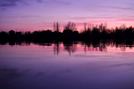 Beautiful colorful dusk on a river. Silhouettes of houses and trees on far bank.