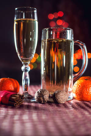 New Years eve. Funny image of a wineglass and a beer glass of champagne, mandarins, cinnamon and walnuts on the background of lights bokeh. Low key. Selective focus.  Stock Photo