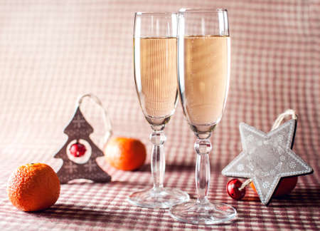 congratulations cards spice: Image of two wineglasses of champagne, decorative wooden star and tree and mandarins on the red checkered background. Rustic style.