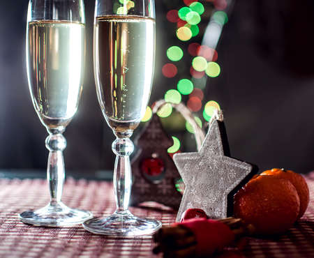 congratulations cards spice: New Years eve. Image of two wineglasses of champagne, decorative wooden star and tree, cinnamon and mandarins on the background of lights bokeh. Low key. Selective focus.  Stock Photo