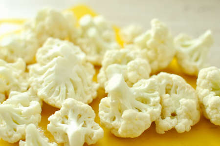 Chopped pieces of cauliflower on yellow cutting board. Prepared raw ingredients for cooking. Stock Photo