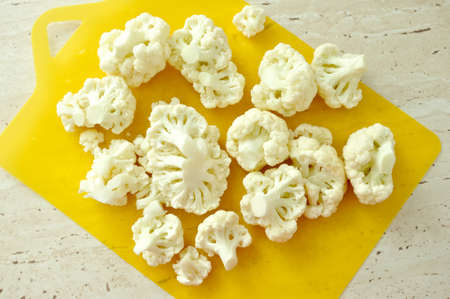 Chopped pieces of cauliflower on yellow cutting board. Prepared raw ingredients for cooking. Top view. Stock Photo