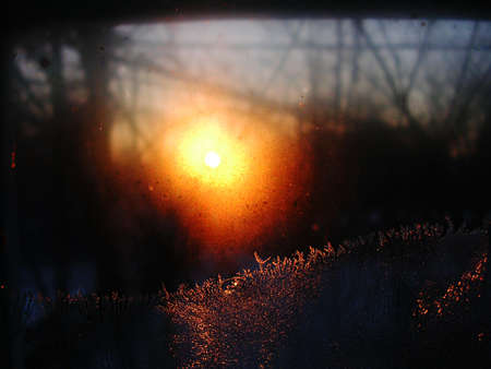 Frost ice crystals and water drops on window glass on the background of rising sun. Close up, contrast vivid colors.