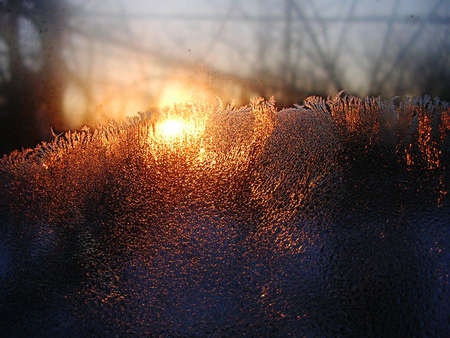 iceflower: Frost ice crystals and water drops on window glass on the background of rising sun. Close up, contrast vivid colors.