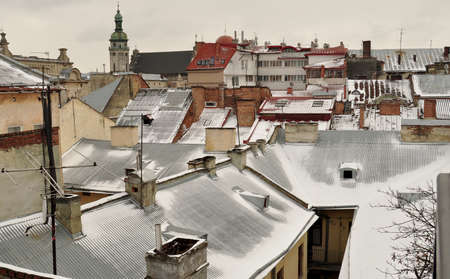snowcovered: Old buildings and snow-covered roofs. Winter view of the downtown in Lviv, Ukraine. Stock Photo
