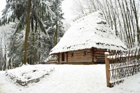 Authentic ukrainian village with wooden huts and fences in winter. Skansen Shevchenkivskyi Hai, Lviv, Ukraine.