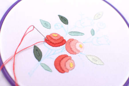 Embroidery with floral motif framed in a hoop. Work in process. Close up, soft selective focus.